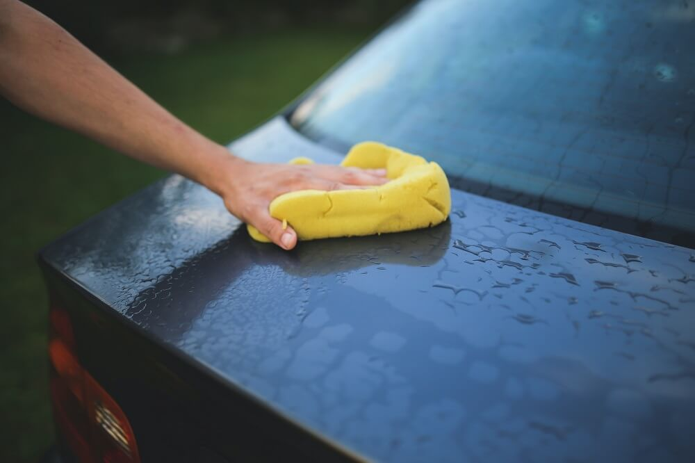 a person holding a sponge and wiping the trunk of the car