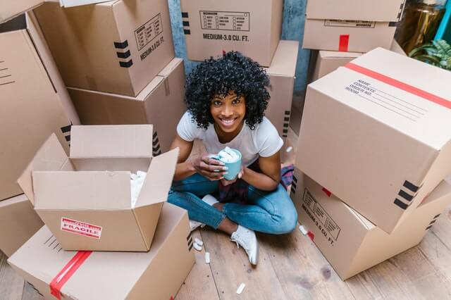 A girl surrounded by moving boxes
