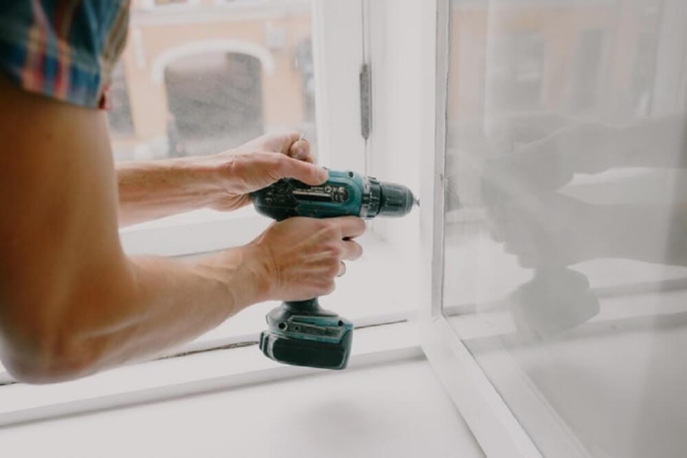 A man screwing a window frame.