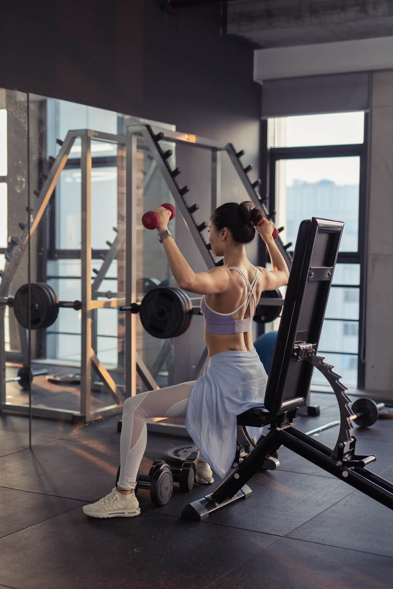 a woman at the gym working out with dumbbells