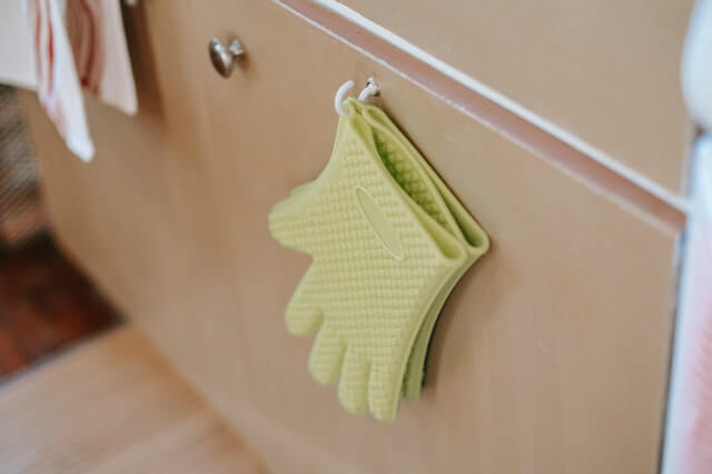An oven glove hanging on a hook outside the cabinet door.