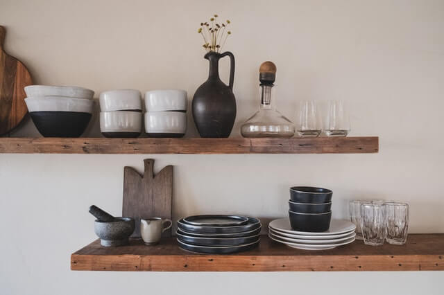 Ceramic dishes on a wooden shelf.