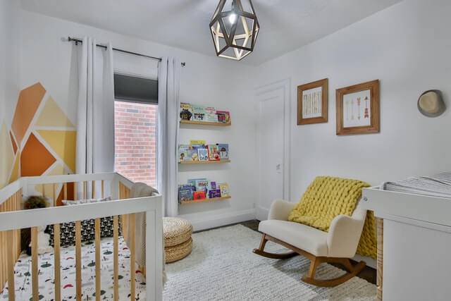 A nursery painted white with a chair, bookshelf and two paintings on the wall.